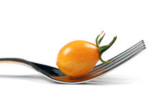 Yellow tomato and fork Royalty Free Stock Images