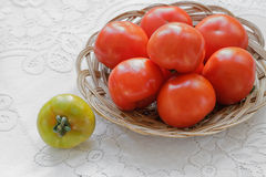 Yellow Tomato. Red Tomatoes in a Bowl and Single Yellow Tomato on a Table. Standing Out From The Crowd Concept Royalty Free Stock Image