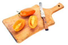 Yellow tomatoe with half slices and old knife on wooden board. Isolated on white background Royalty Free Stock Photos