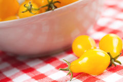 Yellow tomatoes on picnic tablecloth Royalty Free Stock Images