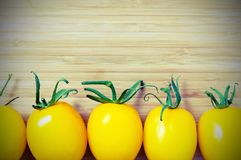 Yellow tomatoes. On wooden background Royalty Free Stock Photo