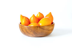 Yellow tomatoes in a wooden bowl. Yellow tomatoes in a wooden bowl on a white background Royalty Free Stock Images