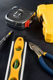 Yellow Tool Box and Tools on Dark Background Stock Photo