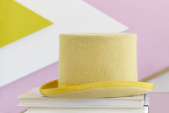 Yellow top hat still life with books and painted wall Stock Photos