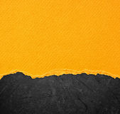 Yellow torn paper over black background Royalty Free Stock Photos