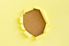 Yellow torn paper over cork board Stock Photography