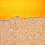 Yellow torn paper with stripes over cork board background. Royalty Free Stock Photography