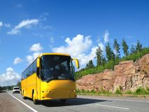 Yellow tourist bus on country highway. Yellow tourist bus on highway Scandinavia Royalty Free Stock Image
