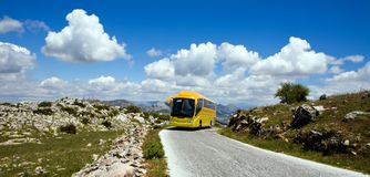 Yellow tourist bus in nature reserve El Torcal Stock Images