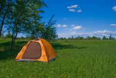 Yellow tourist tent. Stands in shade of trees on  green grass  meadow on  background dark blue sky with clouds Royalty Free Stock Images