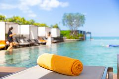 Yellow towel on the bed cushion. By the infinity swimming pool royalty free stock photo
