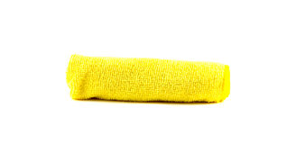 Yellow towel rolled up. On a white background Royalty Free Stock Photography