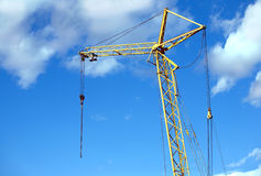Yellow tower construction crane over blue sky with clouds Stock Image