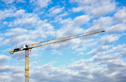 Yellow Tower Crane Against Blue Cloud Sky Stock Photo