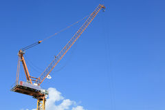 Yellow tower crane against blue sky Stock Photos