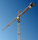 Yellow tower crane against blue sky. Composition with 45 degrees angle royalty free stock image