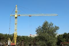 Yellow tower crane against the blue sky and green forest Royalty Free Stock Images