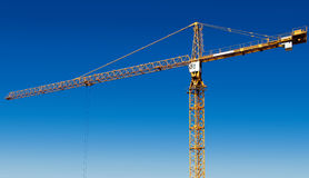 Yellow tower crane against blue sky. Horizontal composition royalty free stock photos