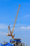 Yellow tower crane on building top Royalty Free Stock Photo