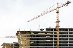 A yellow tower crane lifts building materials to the top of a building. stock photography