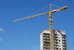 Yellow tower crane at multistory building Stock Photos