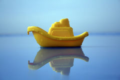 Yellow toy boat. A yellow toy on the blue sea Stock Photos