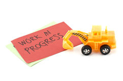 Yellow toy bulldozer with on color paper and blur word work in progress. Stock Photos