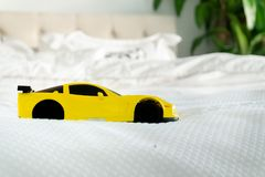 Yellow toy car on bed with white linens stock photo