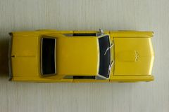 Yellow toy car on gray striped surface. Model  of classic muscle car with shadows and partly soft focus. Top view of auto. Yellow toy car on gray striped surface stock image