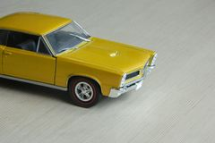 Yellow toy car on gray striped surface. Model of classic muscle car with shadows and partly soft focus. Perspective view of auto royalty free stock image