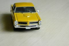Yellow toy car on gray striped surface. Model of classic muscle car with shadows and partly soft focus. Perspective view of  auto. Yellow toy car on gray striped stock photo
