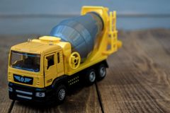 Yellow toy concrete mixer on a wooden background stock image