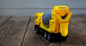 Yellow toy concrete mixer on a wooden background stock photo