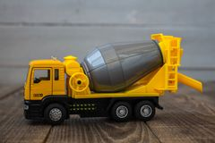 Yellow toy concrete mixer on a wooden background stock images