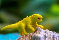 Yellow toy dinosaur on natural shell. Small puppet macro photo. Royalty Free Stock Photo