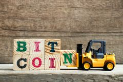 Yellow toy forklift hold letter block N to complete word bitcoin on wood background. Currency digital money crypto symbol cryptocurrency virtual internet stock images