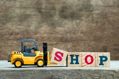 Yellow toy forklift hold letter block S to complete word shop. On wood background royalty free stock image
