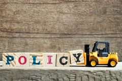 Yellow toy forklift hold letter block Y to complete word policy on wood background stock photo