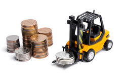 Yellow toy forklift and money. Yellow toy forklift moving stocks of coins Stock Photo