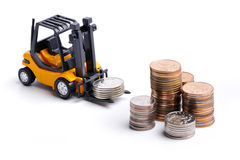 Yellow toy forklift and money. Yellow toy forklift moving stocks of coins Stock Images