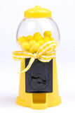 Yellow Gumball Machine. A yellow toy gumball machine with yellow gumballs and a yellow and white checked bow on a white background Royalty Free Stock Photo