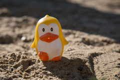 Yellow toy penguin sandbox concept family vacations Stock Image