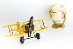 Yellow toy plane with vintage globe map for travel concept royalty free stock image