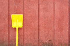 Yellow toy shovel against red barn wall Royalty Free Stock Photos