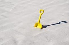 Yellow toy shovel on a beautiful white sand beach. A child yellow toy shovel on a beautiful white sand beach Stock Photo
