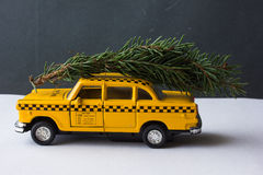 Yellow toy taxi on a tree trunk. Christmas. Stock Images