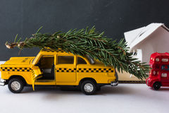 Yellow toy taxi on a tree trunk. Stock Image