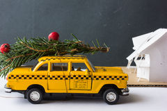 Yellow toy taxi on a tree trunk. Christmas. Stock Photo