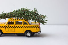 Yellow toy taxi on a tree trunk. Christmas. Stock Photos
