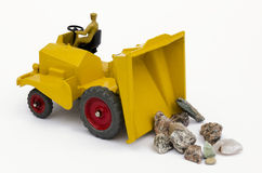 Yellow toy tipper truck and stones. Vintage toy tipper truck tipping stones from bucket. Isolated on a white background Stock Photos